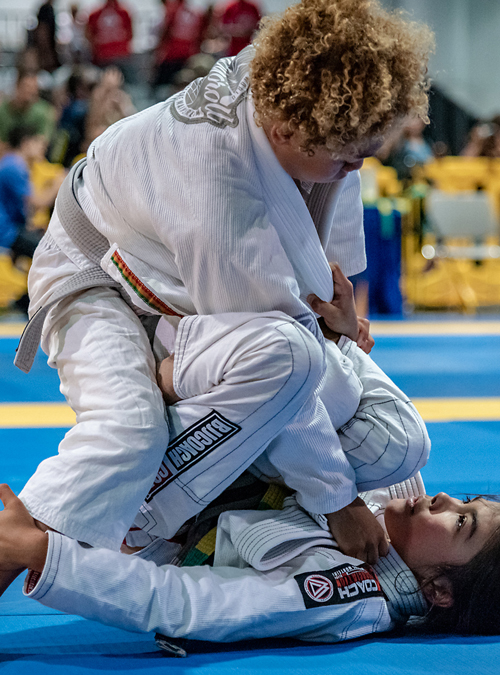 Kid applying a Brazilian Jiu-jitsu sweep on opponent at the IBJJF American National