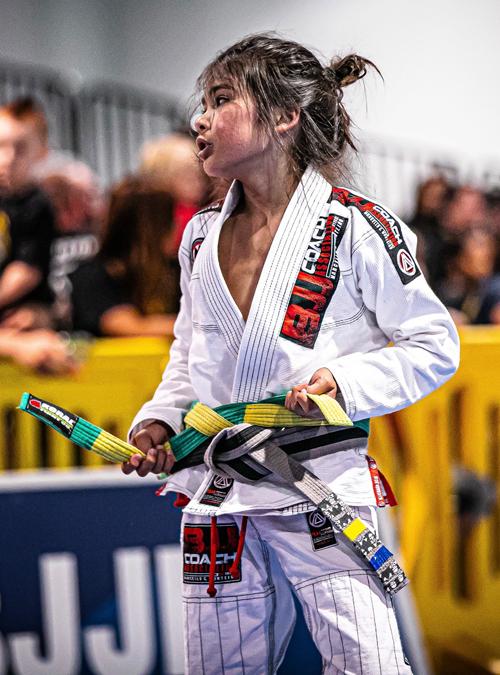 Young kid tying his belt at a Kid's Brazilian Jiu-jitsu tournament