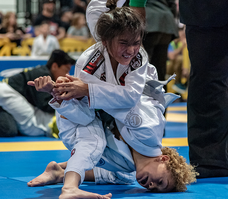 Kid defending a Brazilian Jiu-jitsu shoulder lock attempt at an IBJJF tournament